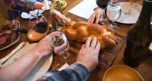 Human hands on challah at Jewish Shabbat, elevated view
